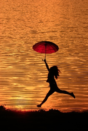 Umbrella woman jumping and sunset silhouette in Lake