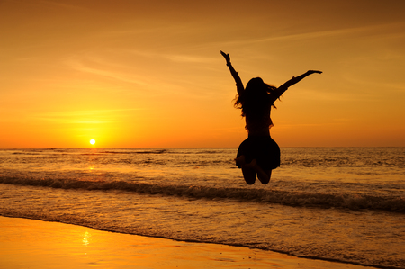 Photo for Happy Woman Jumping in Sea Sunset - Royalty Free Image