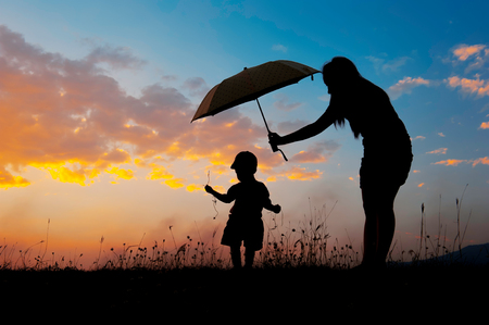 Foto de Silhouette of a mother and son holding umbrella and playing outdoors at sunset silhouette - Imagen libre de derechos