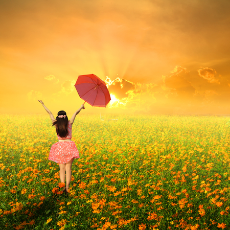 Happy woman holding red umbrella in cosmos flower field and blue sky