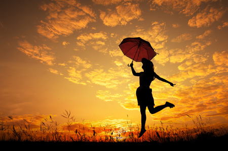 Silhouette of Umbrella woman jump and sunset
