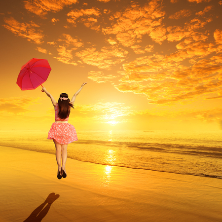 Happy Woman holding umbrella and Jumping in  beach Sunset
