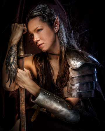 Photo for Portrai of mystic  elf woman with sword, armor and tattoo on her hand. - Royalty Free Image