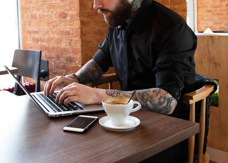 Photo pour Serious man with tattooes working on a laptop in a coffee shop - image libre de droit