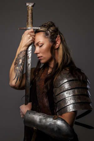 Photo for Elf woman in armor holding sword. Isolated on grey - Royalty Free Image