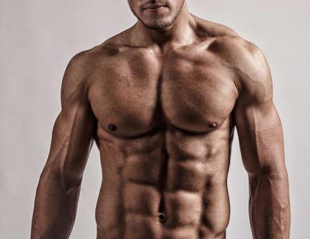 Foto de Portrait in studio of muscular malebody. Isolated on grey background. - Imagen libre de derechos