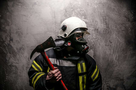 Foto de Firefighter in oxygen mask and axe on grey background. - Imagen libre de derechos