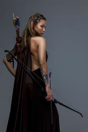Photo for Beautiful elf woman woth bow and arrows. Isolated on grey - Royalty Free Image