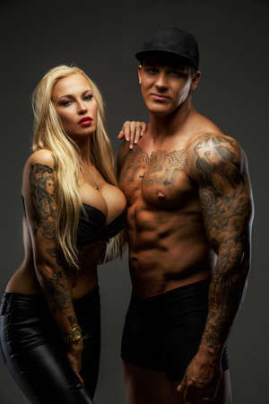 Photo pour Modern couple with tattooed bodies posing in studio - image libre de droit