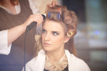 Photo pour Blond female in hair salon. Hairdresser on background - image libre de droit
