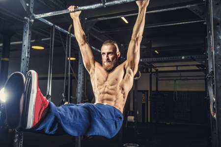 Photo pour Shirtless man with deard in blue pants doing exersices on horizontal bar in a gym. - image libre de droit