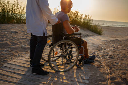 Foto per Young man in wheelchair and his doctor relaxing on the road to the beach. - Immagine Royalty Free