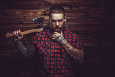Photo for Brutal man with beard and tattooe holding axe over wooden wall. - Royalty Free Image