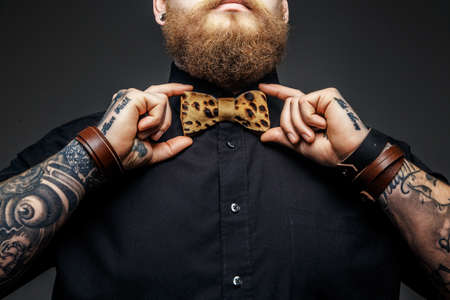 Photo pour Part of man's face with beard and tattooed arms. - image libre de droit