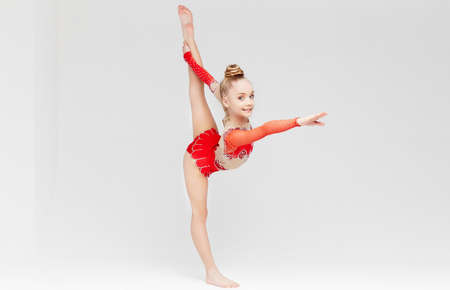 Photo pour Little girl in red dress doing standing split over white background. - image libre de droit