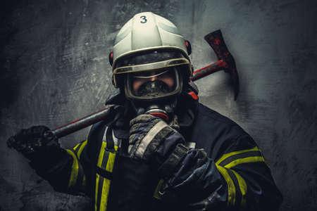 Foto de Rescue firefighter in safe helmet and uniform over grey background. - Imagen libre de derechos