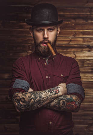 Photo pour Bearded man with tattooes on arms smoking cigar. - image libre de droit