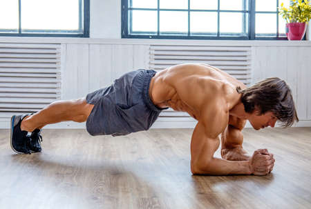 Photo for Sporty male standing on his elbows. Stomach workout. - Royalty Free Image