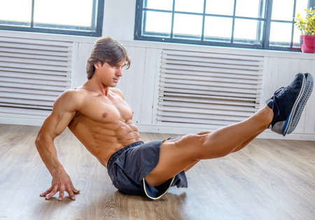 Photo for Suntanned athletic male doing stomach workouts on the floor in natural soft light. - Royalty Free Image