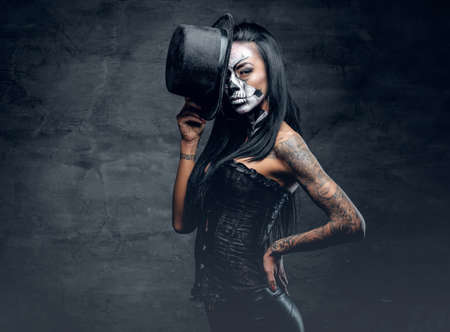 Photo pour A girl in stylish top hat with skull make up and tattoo on arm. Halloween party. - image libre de droit