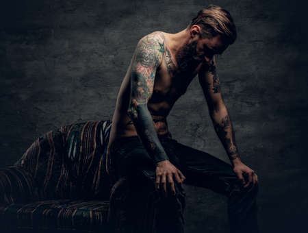 Photo pour The shirtless, tattooed bearded male sits on a chair over grey background. - image libre de droit