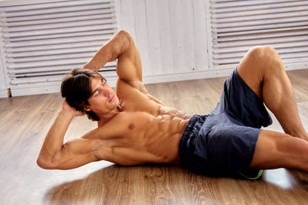 Photo for Suntanned muscular shirtless male doing stomach workouts on a floor in a room. - Royalty Free Image
