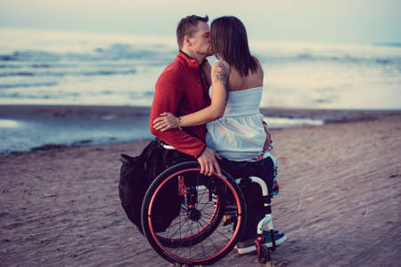 Photo for Handicapped young couple kissing on a beach. - Royalty Free Image