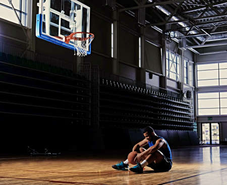 Photo pour Black professional basketball player sits on a field under the hoop in a game hall. - image libre de droit