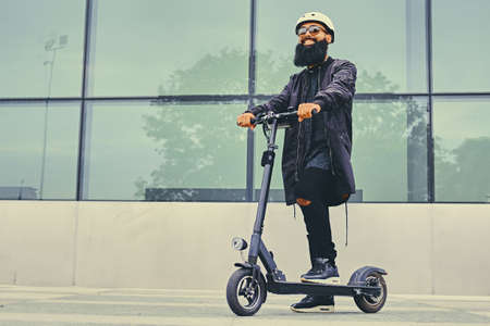 Photo pour Stylish bearded male in sunglasses posing on electric scooter in over modern building background. - image libre de droit