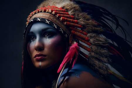 Foto de Close up portrait of shamanic female with Indian feather hat and colorful makeup. - Imagen libre de derechos