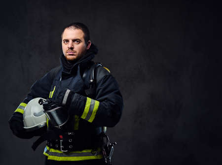 Photo for Studio portrait of firefighter dressed in uniform holds safety helmet in his arm. - Royalty Free Image