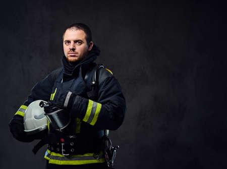 Photo pour Studio portrait of firefighter dressed in uniform holds safety helmet in his arm. - image libre de droit