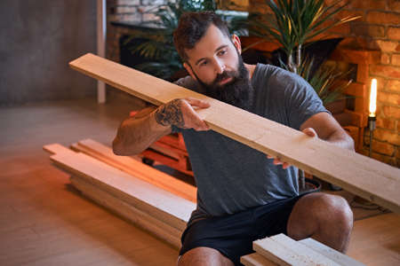 Photo for Carpenter checks the boards in a loft room. - Royalty Free Image