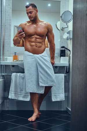Photo pour A handsome muscular male in stylish twin bathroom. - image libre de droit