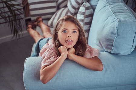 Foto de Portrait of a happy little girl with long brown hair and piercing glance, shows tongue on the camera, lying on a sofa at home - Imagen libre de derechos