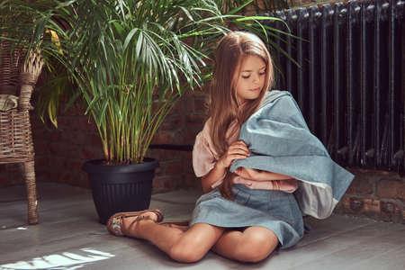 Foto de Cute little girl with long brown hair wearing a stylish dress, sitting on a wooden floor in a room with a loft interior - Imagen libre de derechos