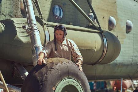 Foto de Mechanic in uniform and flying helmet wash large military helicopter. - Imagen libre de derechos