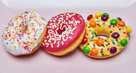 Photo for Three appetizing donuts lie on a pink ceramic plate. - Royalty Free Image