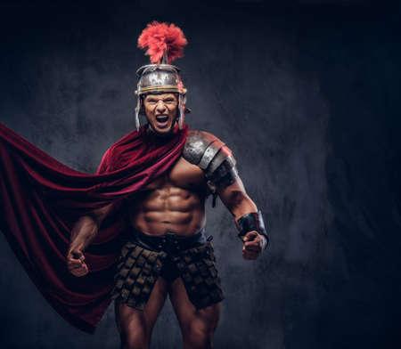 Foto de Brutal ancient Greece warrior with a muscular body in battle uniforms screams in battle agony - Imagen libre de derechos