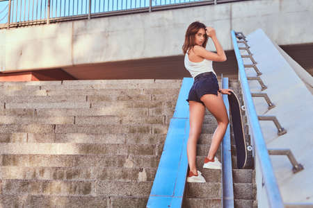 Photo for Back view of a sensual sexy girl dressed in shorts and t-shirt holds a skateboard posing at camera while standing on steps. - Royalty Free Image