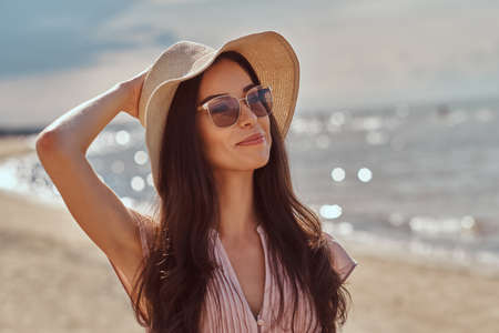 Photo for Portrait of a smiling beautiful brunette girl with long hair in sunglasses and sunglasses wearing a dress on the beach. - Royalty Free Image