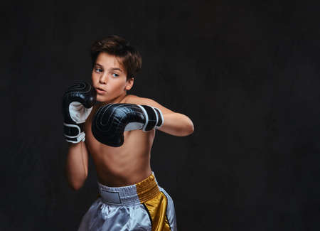 Photo for Handsome shirtless young boxer during boxing exercises, focused on process with serious concentrated facial. Isolated on the dark background. - Royalty Free Image