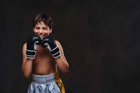 Photo for Happy handsome shirtless young boxer wearing gloves. Isolated on a dark background. - Royalty Free Image