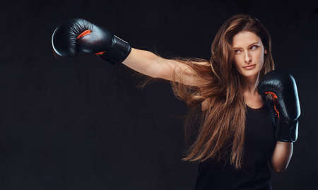 Photo pour Beautiful brunette female boxer during boxing exercises, focused on a process with serious concentrated facial. - image libre de droit