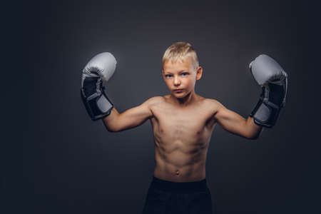 Photo for Young shirtless boy boxer with boxing gloves posing in a studio. - Royalty Free Image