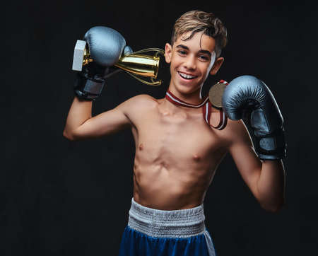 Photo for Joyful young shirtless boxer champion wearing gloves holds a winners cup and the gold medal. Isolated on a dark background. - Royalty Free Image
