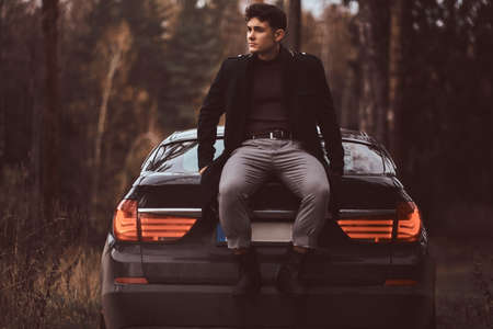 Photo for A stylish young man wearing a black coat sitting on the trunk of a car in the autumn forest - Royalty Free Image