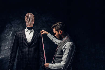 Photo pour A young fashion designer with a measuring tape check the length of the sleeves of a custom made elegant mens suit in a dark tailor studio. - image libre de droit