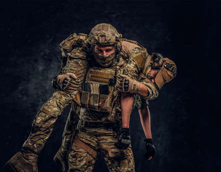 Foto de Combat conflict, special mission, retreat. Soldier special forces rescue his wounded teammate carrying him on his shoulders from the battlefield. Studio photo against a dark wall - Imagen libre de derechos