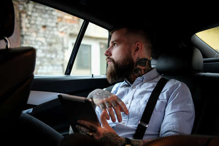 Foto für Self-confident bearded man is sitting in the car. He is wearing shirt and suspender. He has tattoes on his arms and neck. Man is holding a tablet and looking to the window. - Lizenzfreies Bild